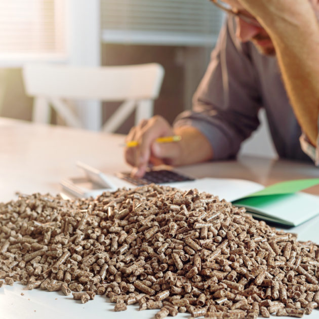 Man calculating household heating costs. Wooden pellets, biomass, effective, environmentally friendly and economical heating, sustainable and renewable energy